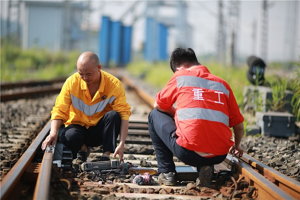 Workers carry out rail inspection under scorching heat